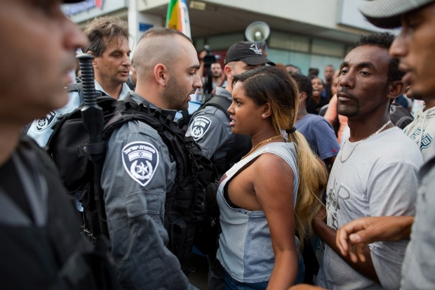 Ethiopian Israeli protestors scuffle with Israeli police during a demonstration against police brutality and racism, in the centre of Tel Aviv on June 22, 2015. More than 135,000 Ethiopian Jews live in Israel, having immigrated to the Jewish state in two waves in 1984 and 1991. AFP PHOTO / MENAHEM KAHANA / AFP / MENAHEM KAHANA