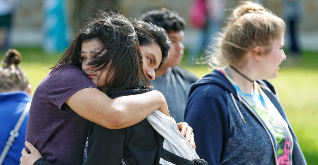 Santa Fe High School freshman Caitlyn Girouard, center, hugs her friend outside the Alamo Gym where students and parents wait to reunite following a shooting at Santa Fe High School Friday, May 18, 2018 in Santa Fe. ( Michael Ciaglo / Houston Chronicle )