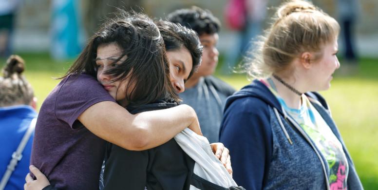Santa Fe High School freshman Caitlyn Girouard, center, hugs her friend outside the Alamo Gym where students and parents wait to reunite following a shooting at Santa Fe High School Friday, May 18, 2018 in Santa Fe. ( Michael Ciaglo / Houston Chronicle )